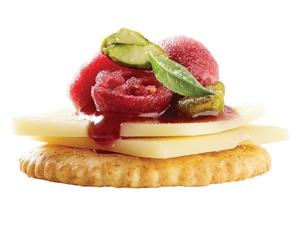Cracker topped with cheese slice, raspberry jam, pistachios, candied cranberries and mint leaf