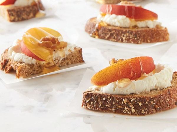 Bread topped with goat cheese, peach slices, honey, and walnuts