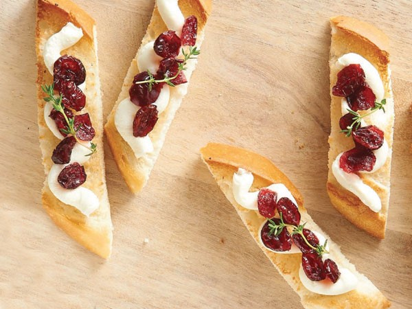 Wooden plank of cranberry-mascarpone toasts