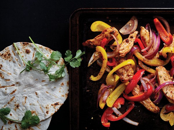 Pan of fajita-seasoned chicken and vegetables served with soft shell tortillas and cilantro