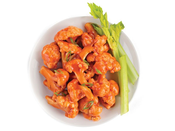 Plate of cauliflower bites covered in buffalo sauce served with celery