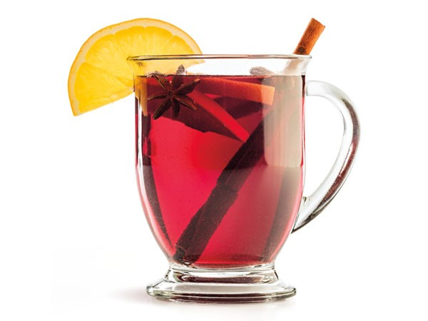 Glass of mulled wine, garnished with cinnamon sticks, star anise and lemon slices