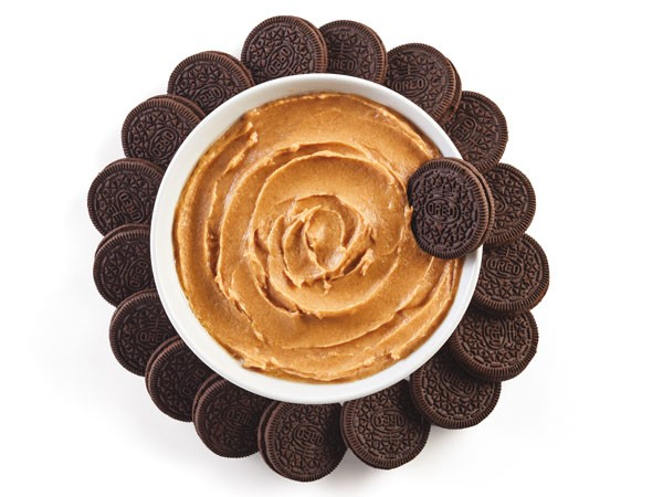 Peanut butter dip surrounded by chocolate cookie sandwiches