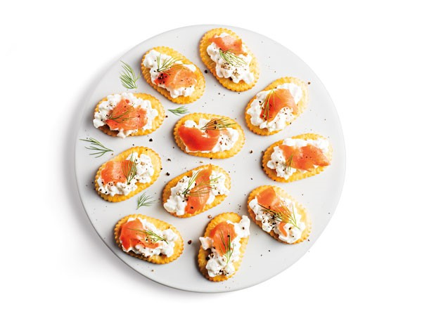 Platter of oval crackers topped with cottage cheese, smoked salmon and sprigs of fennel