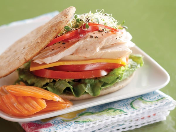 Honey wheat sandwich thin filled with rotisserie chicken slices, tomatoes, ranch, cheddar cheese, bell pepper and lettuce on a white plate