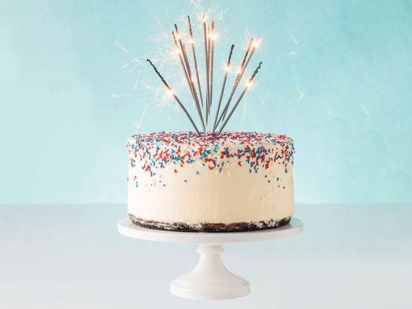 Vanilla ice cream cake topped with red, white and blue sprinkles and garnished with sparklers