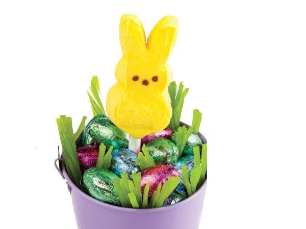 Purple bucket filled with green licorice, Easter egg-shaped candy and a yellow peep on a popsicle stick