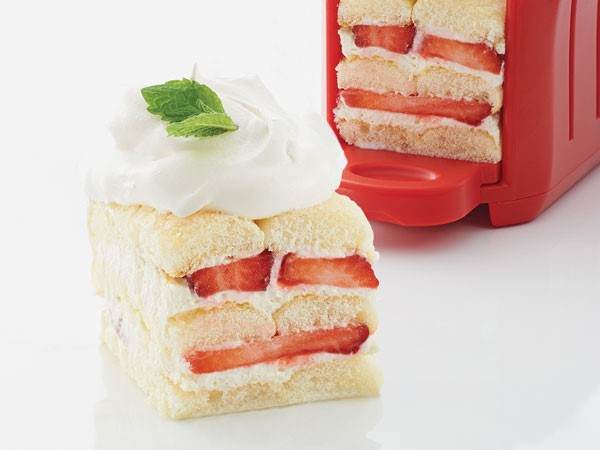 Ladyfingers piled together, filled with cream and fresh strawberries and garnished with a dollop of whipped topping and a mint leaf