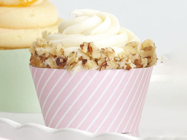 Carrot-walnut cupcake garnished with crushed walnuts in a pink muffin liner