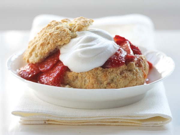 Shortcake garnished with whipped topping and fresh strawberries