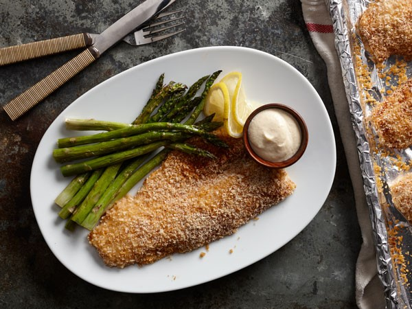 Plate of breaded walleye, served with side of asparagus, lemon slices and aioli