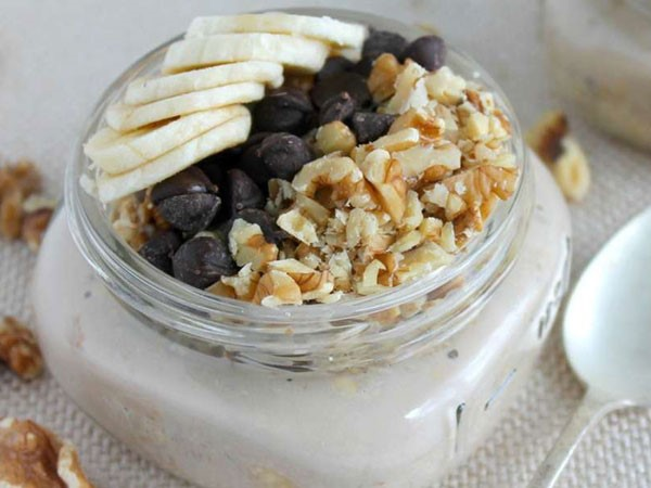 Mason jar filled with overnight oatmeal, topped with sliced bananas, chocolate chips and walnuts