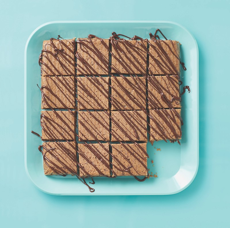 Blue tray of chocolate-peanut butter protein bars drizzled in chocolate with one missing square