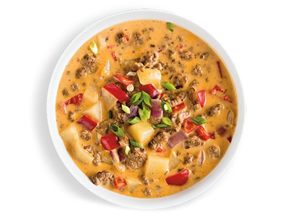 Bowl of cheeseburger chowder garnished with green onions and red bell peppers