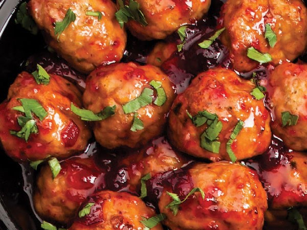 Slow-Cooker filled with Meatballs covered in Cranberry Sauce