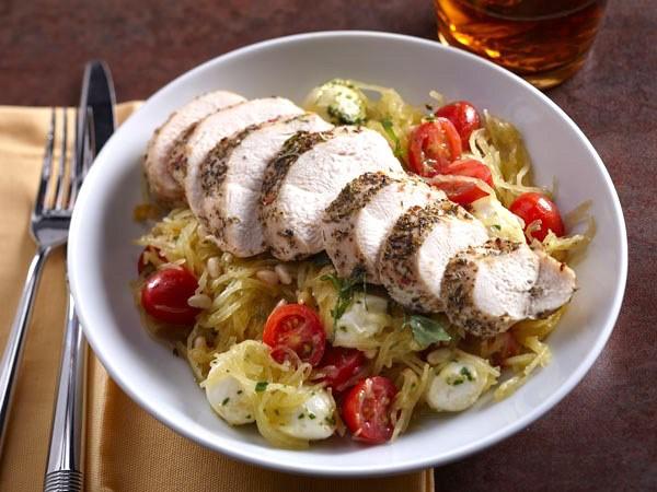 Bowl of sliced chicken over spaghetti, squash, tomatoes and mozzarella