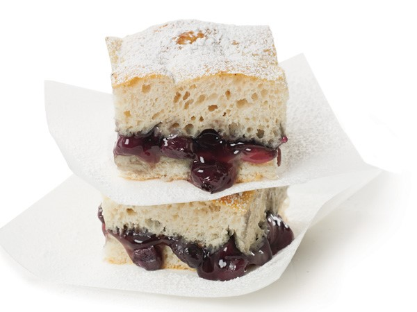 Stack of blueberry cobbler bars between layers of parchment paper