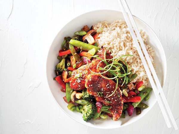White bowl of stir-fry chicken tenders and vegetables, served with a side of rice and chopsticks