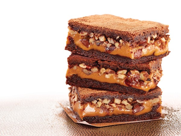 Caramel-pecan brownies stacked on parchment paper