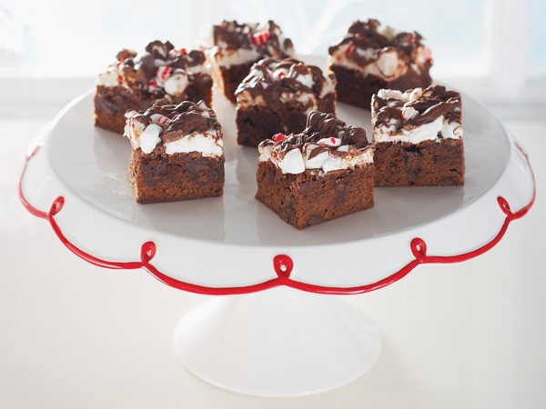 Chocolate chip brownie squares topped with mini marshmallows, crushed candy canes and drizzled melted semisweet chocolate chips on a white cake stand