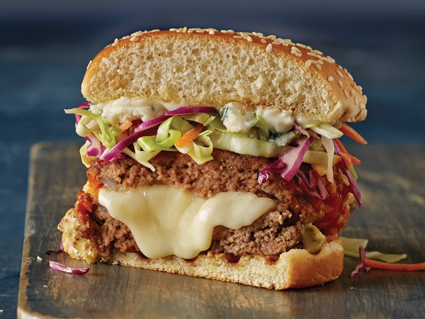 Burger stuffed with oozing cheese and topped with fresh vegetable tricolored slaw