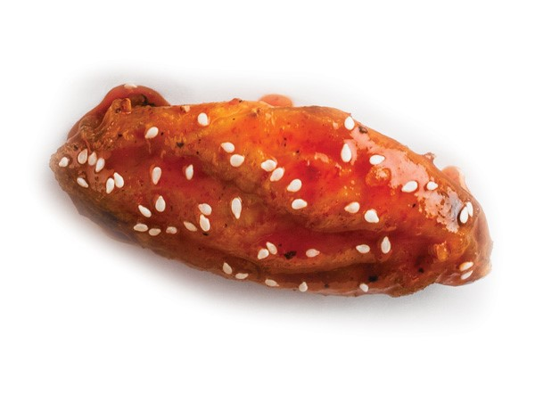 Chicken wing coated in sriracha sauce and sprinkled with sesame seeds