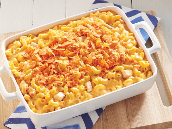 White casserole dish of buffalo chicken mac 'n' cheese topped with crushed Doritos nacho cheese flavored chips