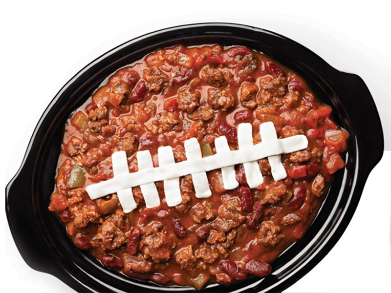 Slow-cooker filled with beef and bean chili with piped sour cream football lace down the center of the dish