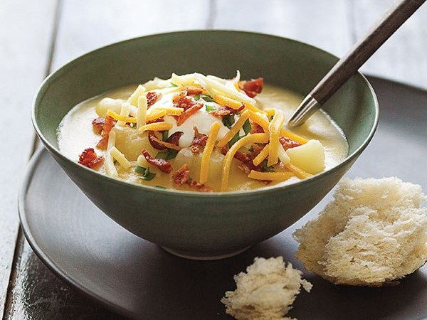 Bowl of potato soup garnished with a dollop of sour cream, shredded cheese, bacon bits and chive and served with bread