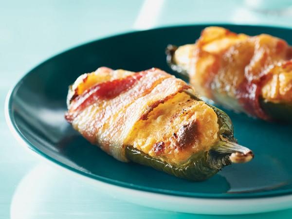 Bacon-wrapped stuffed jalapenos on a blue plate