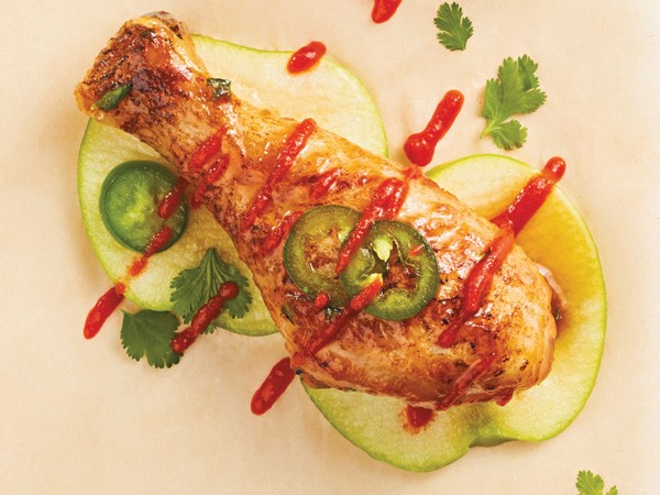 Jalapeno chicken drumsticks drizzled in sauce served over apples with cilantro and jalapeno slices
