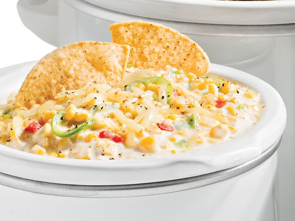 Corn dip with jalapenos, bacon, parmesan and chives served in a slow cooker