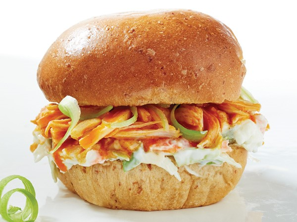 Shredded chicken with buffalo sauce and coleslaw sandwiched between a bun