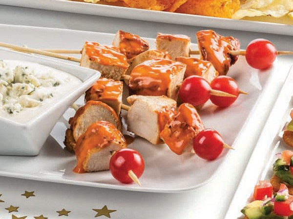 Buffalo chicken skewers with cherry tomatoes and side dish of bleu cheese dip