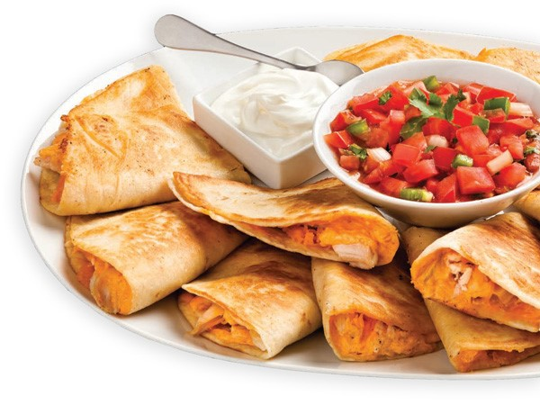 Quesadillas filled with chicken, cheese, and buffalo sauce on a white plate with sides of sour cream and pico de gallo