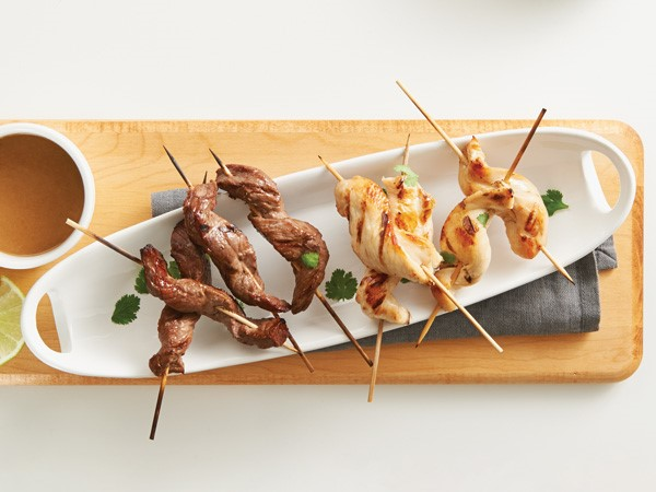White platter of beef and chicken satay on wooden skewers garnished with cilantro