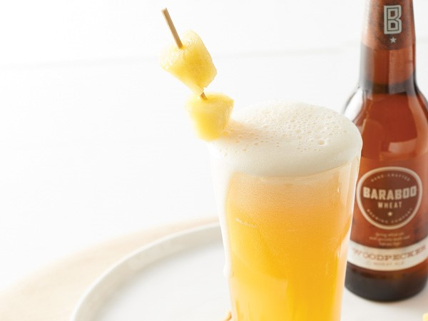 Glass of beer and bourbon cocktail with skewered pineapple chunks