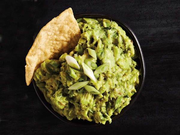 Guacamole garnished with a tortilla chip and green onions
