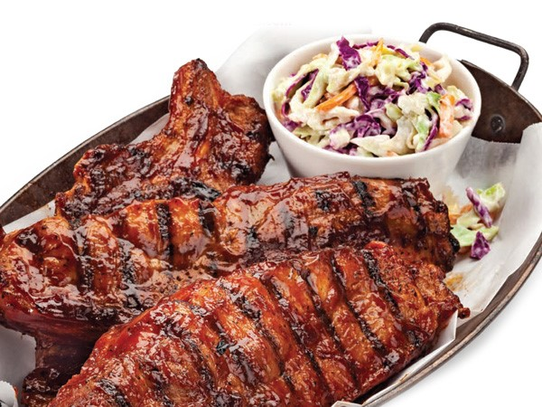 Dish of saucy country pork ribs with side of coleslaw