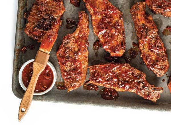 Platter of barbecue ribs with side of barbecue sauce and brush