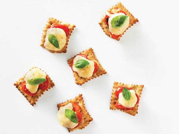 Crackers topped with tomato, mozzarella and basil