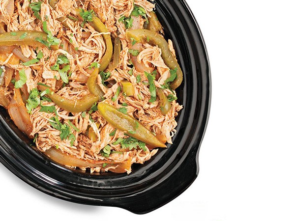 Slow cooker filled with chicken fajita meat and garnished with sliced green bell peppers and cilantro