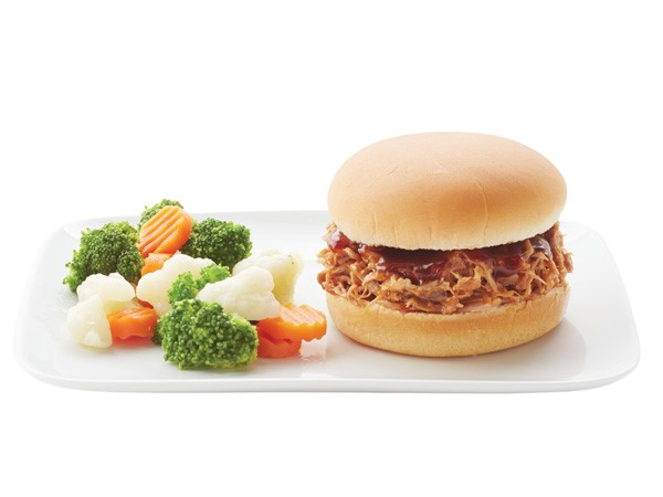 BBQ pulled pork sandwich on a white plate with veggies