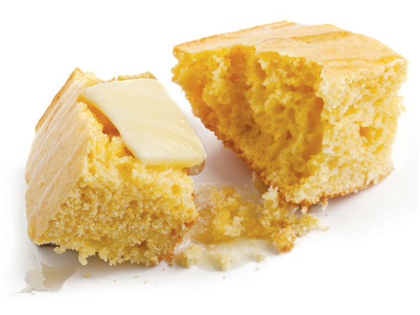 Piece of cornbread pulled apart with square of butter on top