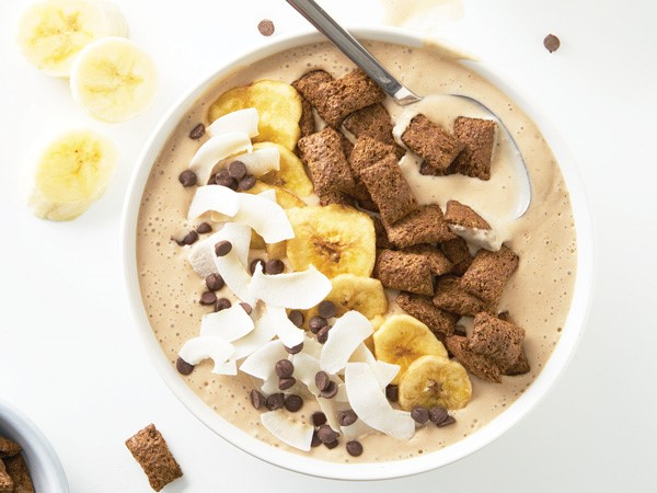 Smoothie bowl topped with mini chocolate chips, coconut flakes, banana chips, and chocolate cereal