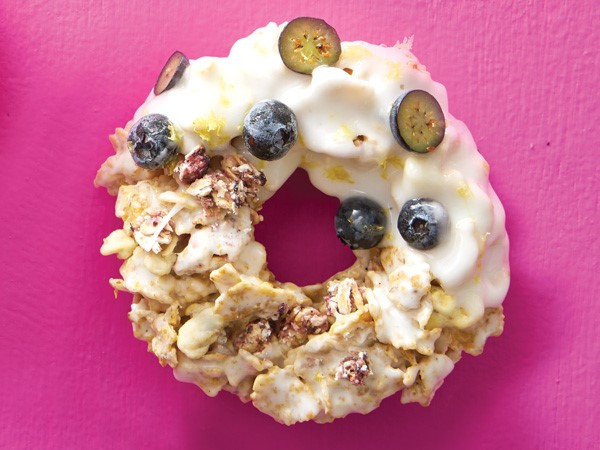 Cereal donut on a pink background with half dipped into glaze with lemon zest and halved blueberries on top
