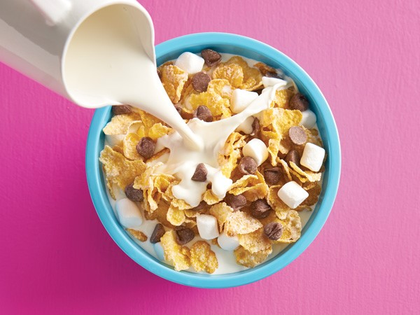 Flaked corn cereal with mini marshmallows and chocolate chips with milk being poured into blue bowl