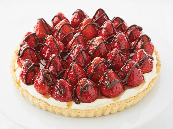 Tart topped with whole glazed strawberries drizzled with chocolate