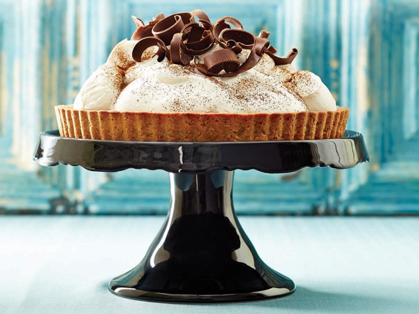 Coffee cream chocolate tart garnished with cocoa powder and chocolate shavings on a cake stand