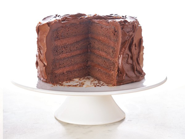 Cake stand filled with chocolate buttercream layer cake with a slice cut out